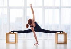 La giovane donna bella pratica il asana di yoga allo studio di yoga Fotografia Stock Libera da Diritti