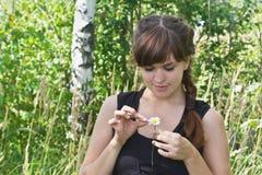 La giovane donna bella si domanda sul fiore Immagini Stock Libere da Diritti