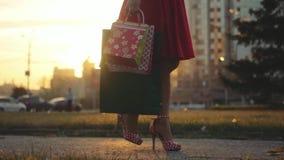 La giovane donna in bello vestito con i sacchetti della spesa va sulla via attraverso il sole durante il tramonto al rallentatore archivi video