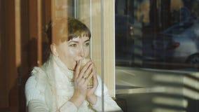 La giovane donna beve il caffè in caffè Ritratto della donna caucasica con la sciarpa della lana del pizzo che gode dell'aroma de archivi video