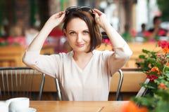 La giovane donna beve il caffè in self-service e la posa con gli occhiali da sole Fotografia Stock Libera da Diritti