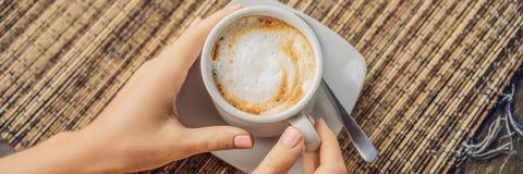 La giovane donna beve il caffè in un caffè nell'INSEGNA delle montagne, FORMATO LUNGO fotografia stock