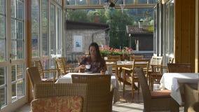 La giovane donna beve il caffè in un ristorante stock footage