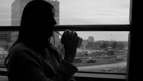 La giovane donna beve il succo di recente schiacciato in un caffè, guardante fuori la finestra sui precedenti della megalopoli fotografia stock libera da diritti