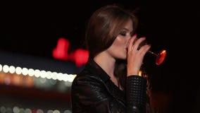 La giovane donna beve una bevanda alcolica da vetro che tiene in sua mano all'aperto archivi video