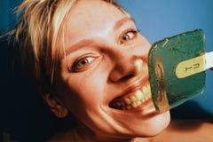 La giovane donna bianca al sorriso di divertimento del partito lecca il verde della lecca-lecca Fotografia Stock Libera da Diritti