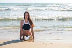 La giovane donna in bikini fa il asana di yoga di Bhujangasana o la posa sulla spiaggia soleggiata, vista frontale della cobra Immagine Stock Libera da Diritti