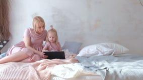 La giovane donna bionda attraente con la sua piccola figlia affascinante nel rosa veste la sorveglianza del qualcosa in compressa archivi video
