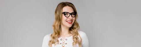 La giovane donna bionda attraente di affari in bianco e nero copre sorridere mostrando la lavagna per appunti in sue mani che sta immagini stock libere da diritti