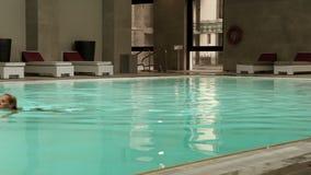 La giovane donna bionda attraente ha un nuoto di sera nello stagno di benessere video d archivio