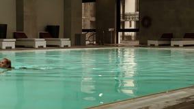 La giovane donna bionda attraente ha un nuoto di sera nello stagno di benessere archivi video