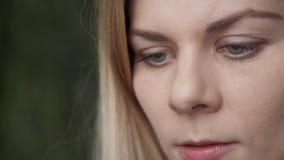La giovane donna bionda con i cavi regolari dei capelli guarda con un fronte diritto archivi video