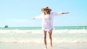 La giovane donna bionda con il cappello e la tunica bianca si muove sulla spiaggia tailandese stock footage