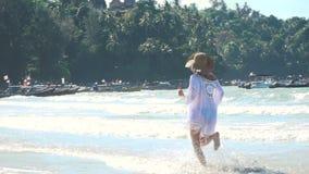 La giovane donna bionda con il cappello e la tunica bianca si muove sulla spiaggia tailandese video d archivio