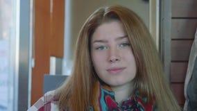 La giovane donna bionda dai capelli lunghi esamina tranquillamente la macchina fotografica video d archivio