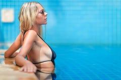 La giovane donna bionda esile con capelli lunghi in occhiali da sole ottiene l'abbronzatura immagine stock