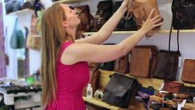 La giovane donna bionda felice in negozio sceglie le borse di mano archivi video