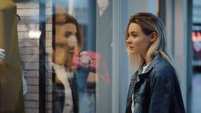 La giovane donna bionda incantevole sta prima di una finestra di manifestazione nel centro commerciale stock footage
