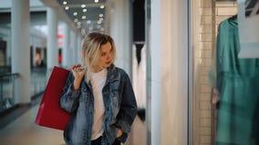 La giovane donna bionda premurosa cammina lungo una finestra di manifestazione con le borse nel centro commerciale stock footage