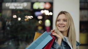 La giovane donna bionda in rivestimento dei jeans cammina intorno ad un centro commerciale con le borse variopinte stock footage