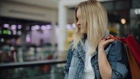 La giovane donna bionda in rivestimento dei jeans cammina intorno ad un centro commerciale con le borse variopinte video d archivio