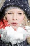 La giovane donna bionda soffia in una manciata di neve Fotografia Stock