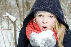 La giovane donna bionda soffia in una manciata di neve Immagini Stock
