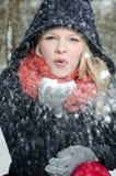 La giovane donna bionda soffia in una manciata di neve Fotografia Stock Libera da Diritti