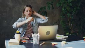 La giovane donna bionda sta sedendosi nell'ufficio che lavora con il computer È stanca in modo da sta toccando il suoi fronte e c video d archivio