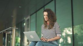 La giovane donna in camicia a strisce facendo uso del suo computer portatile fuori, inclina giù video d archivio
