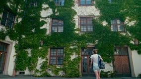 La giovane donna cammina con lo zaino nel cortile del castello di Mikulov con l'edera sulle pareti archivi video