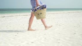 La giovane donna cammina a piedi nudi sulla spiaggia lungo l'oceano video d archivio