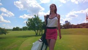 La giovane donna cammina su un campo da golf, tenente una borsa con attrezzatura archivi video