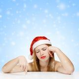 La giovane donna in cappello del Babbo Natale che posa con stancato considera blu Fotografia Stock