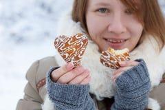 La giovane donna in cappotto dell'inverno ed i guanti grigi tricottati tengono il beautif Immagine Stock Libera da Diritti