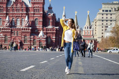 La giovane donna in cappotto giallo cammina sul quadrato rosso a Mosca Fotografie Stock