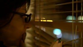 La giovane donna castana alla notte spinge i ciechi guarda fuori la finestra con attenzione, ottiene spaventata immagini stock