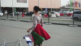 La giovane donna castana in bello vestito con i sacchetti della spesa va sulla via al rallentatore 1920x1080 archivi video