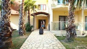 La giovane donna castana in breve e talloni viene con la valigia fra le palme in hotel di estate Festa e vacanza video d archivio