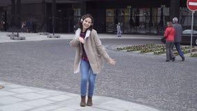 La giovane donna castana in cuffie sta ballando video d archivio