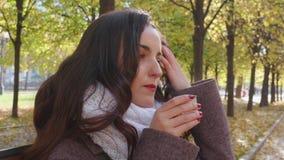 La giovane donna castana del sud in cappotto grigio sta bevendo la bevanda calda dalla tazza del termos nel parco di autunno archivi video