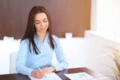 La giovane donna castana di affari assomiglia ad una ragazza dello studente che lavora nell'ufficio Ragazza ispana o dell'America Fotografia Stock