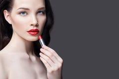 La giovane donna castana dipinge il suo rossetto rosso luminoso delle labbra Trucco luminoso di sera Ragazza nuda che prende cura Fotografia Stock Libera da Diritti