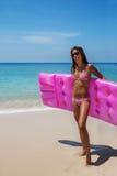 La giovane donna castana esile in occhiali da sole prende il sole sulla spiaggia tropicale immagini stock libere da diritti