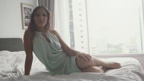 La giovane donna castana felice che ondeggia sulla video chiacchierata si siede sul letto in appartamento 3840x2160 archivi video