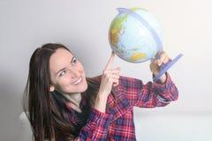 La giovane donna castana felice sogna del viaggio sulla vacanza con un globo in mani su un sofà bianco nella stanza Immagine Stock