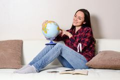 La giovane donna castana felice sogna del viaggio sulla vacanza con un globo in mani su un sofà bianco nella stanza Fotografie Stock