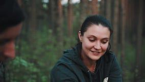La giovane donna castana in maglia con cappuccio verde parla con amico maschio in foresta al picnic stock footage