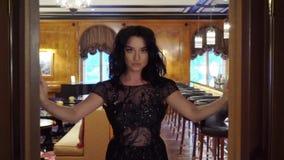 La giovane donna castana sexy in vestito uguagliante nero apre le porte archivi video
