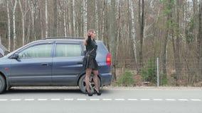 La giovane donna castana si ferma per un giro vicino alla macchina rotta stock footage